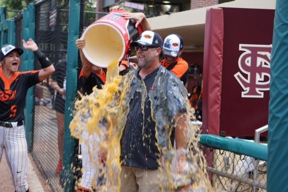 Photo -  Oklahoma State coach Kenny Gajewski smiles as he is doused with a bucket of some orange sports drink after beating Florida State 3-2 Saturday. [PHOTO COURTESY OF OSU ATHLETICS]