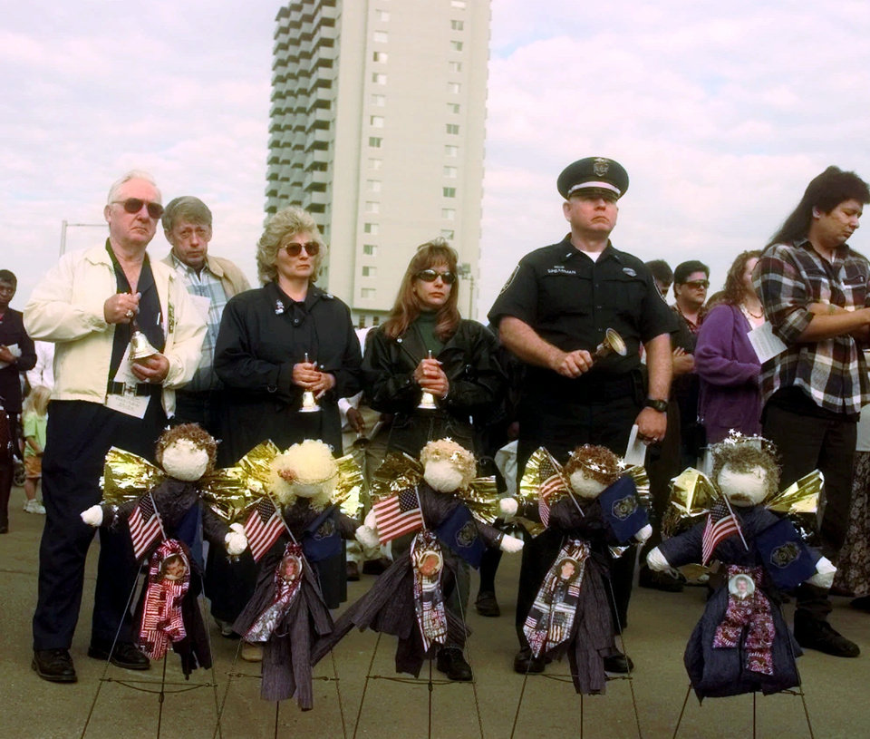 Photo - Friends and relatives of law enforcement officers killed in the Alfred Murrah Federal Building car bomb explosion stand behind memorial wreaths Sunday, April 19, 1998, during a memorial ceremony marking the third anniversary of the bombing. (AP Photo/Jerry Laizure)