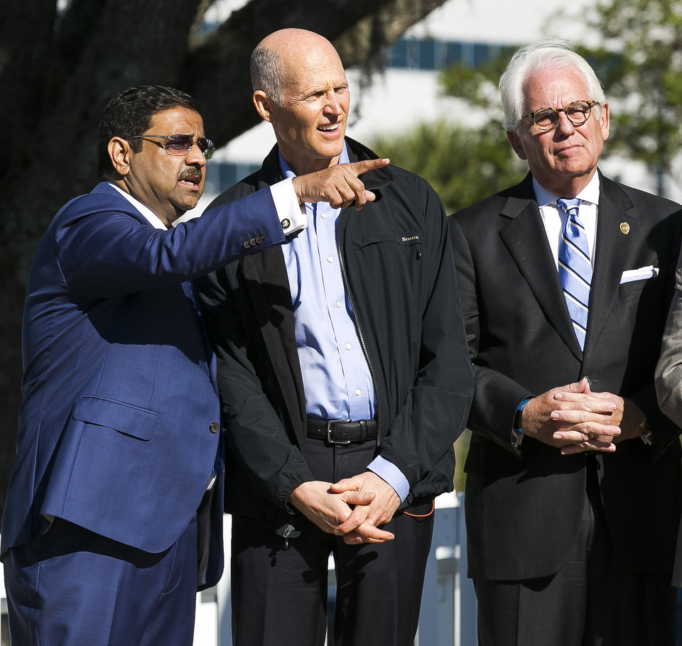 Photo -  FILE - In this March 23, 2018 file photo, developer Danny Gaekwad, left, points in the direction where his hotel will be built while talking with Florida Governor Rick Scott, center, as Ocala Mayor Kent Guinn listens in downtown  Ocala, Fla.  Since the coronavirus crisis started, hotel owners say they are struggling to get relief on a type of loan that Wall Street investors buy.  [Doug Engle/Ocala Star-Banner via AP)