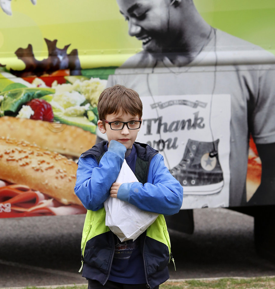 Photo - Students receive sack lunches from a food truck provided by Oklahoma City Public Schools Nutrition Services on Monday, April 2, 2018. As a result of the teacher walkout, children who spent their day at the Boys and Girls Club of Oklahoma County  received free lunches from the school district. Photo by Jim Beckel, The Oklahoman