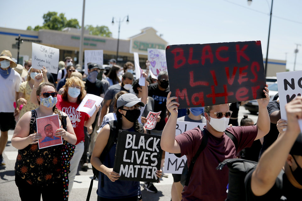 Photo - Protesters march across 2nd Street during a protest in Edmond, Okla., Saturday, June 6, 2020. The protest was organized in response to the shooting death of Isaiah Lewis by Edmond Police last year and the death of George Floyd in Minneapolis. [Bryan Terry/The Oklahoman]
