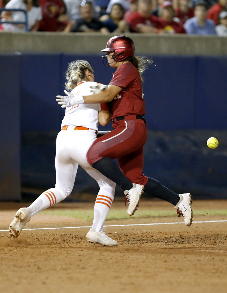 Photo - Oklahoma's Nicole Mendes (11) runs into Oklahoma State's Sydney Pennington (21) in the 6th innning during a Women's College World Series between Oklahoma State (OSU) and Oklahoma at USA Softball Hall of Fame Stadium in Oklahoma City,  Friday, May 31, 2019.  [Sarah Phipps/The Oklahoman]