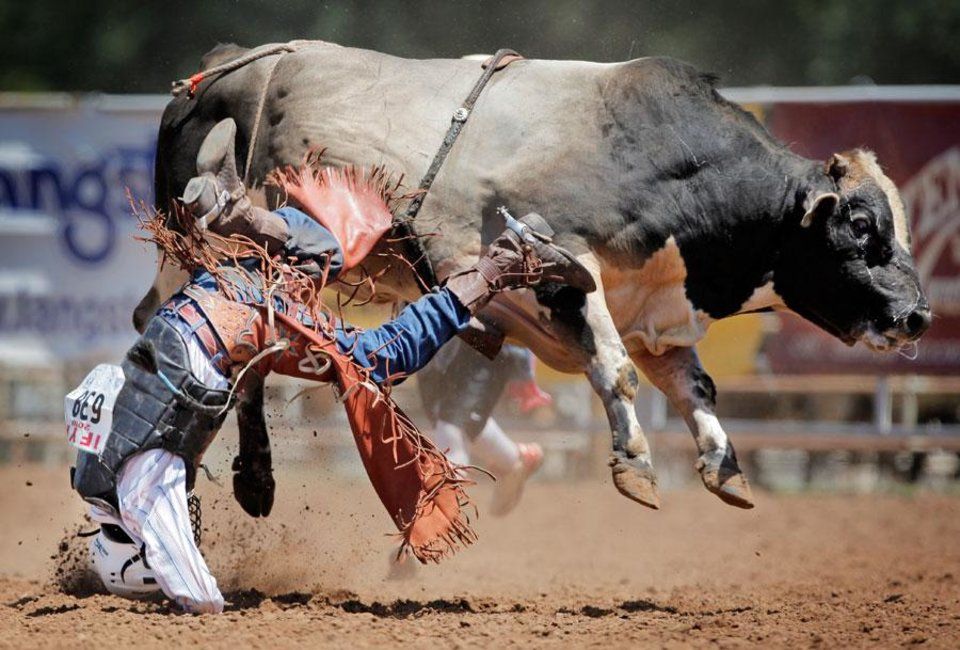 Photo -  Clint Miller of Sulphur, Oklahoma, hits the ground while competing in bull riding during the final round of the International Finals Youth Rodeo (IFYR) in Shawnee, Okla., Saturday, July 17, 2010. Photo by Nate Billings, The Oklahoman