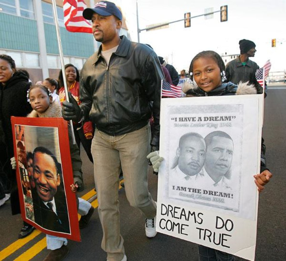 Dennis Lewis and his nieces Paula Jones, 8, and Nesha Henderson, 9, march in the Martin Luther King Jr. Day parade in Oklahoma City, Monday, January 19, ...