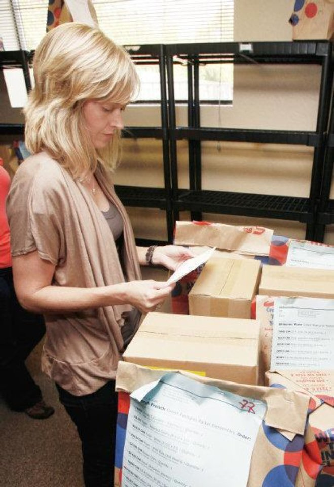 Photo - Lee Ann Chandler, program director for the Teachers Warehouse, double-checks orders for the half-dozen teachers picking up free supplies Friday. The program gives away about $40,000 worth of supplies every month.  Steve Gooch - The Oklahoman
