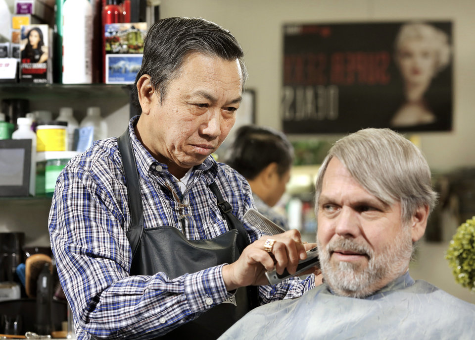 Photo -  Hank's Barber Shop owner Ky Nguyen gives a haircut to customer Jim Griffy on Tuesday.