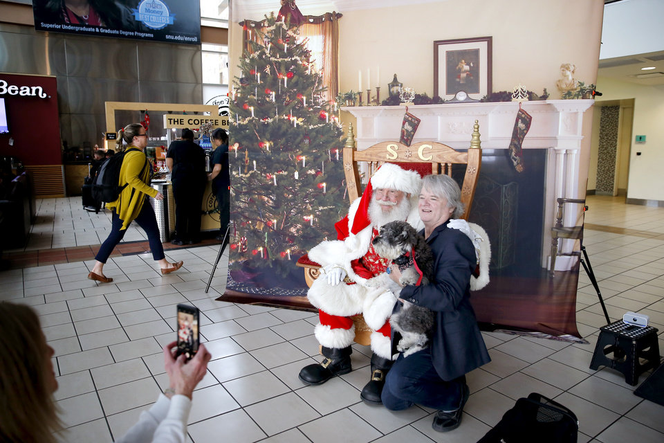 Photo -  Hodd Whicker of Lawton and his dog, The Mouse, pose for a photo with Santa Claus on Tuesday inside Will Rogers World Airport. [Photo by Bryan Terry, The Oklahoman]