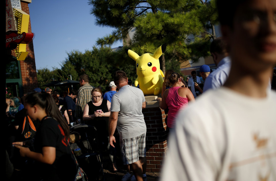 Photo - People play Pokemon Go during a meetup for players of the game in Oklahoma City at Bricktown on Friday, July 29, 2016. Photo by Bryan Terry, The Oklahoman