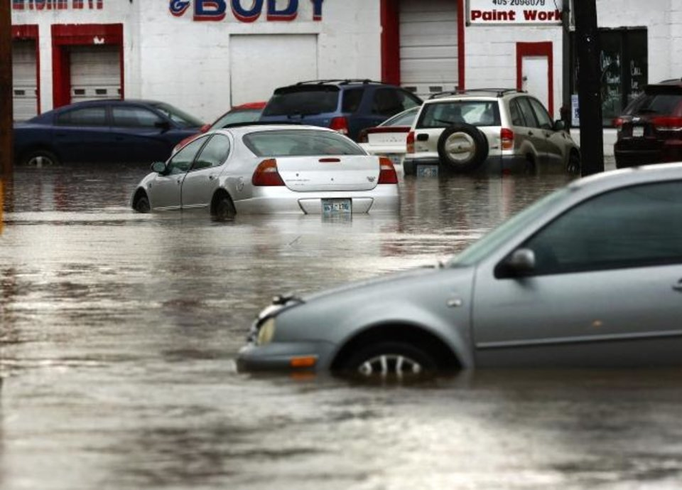 Photo -  Heavy rains overwhelmed stormwater drainage systems and caused flooded streets, requiring  high water rescues in Oklahoma City as another round of severe storms passes through the metro on Thursday.  [Jim Beckel/The Oklahoman]