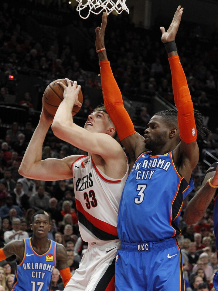 Photo - Portland Trail Blazers forward Zach Collins, front left, shoots as Oklahoma City Thunder forward Nerlens Noel, right, defends during the second half of Game 1 of a first-round NBA basketball playoff series in Portland, Ore., Sunday, April 14, 2019. (AP Photo/Steve Dipaola)