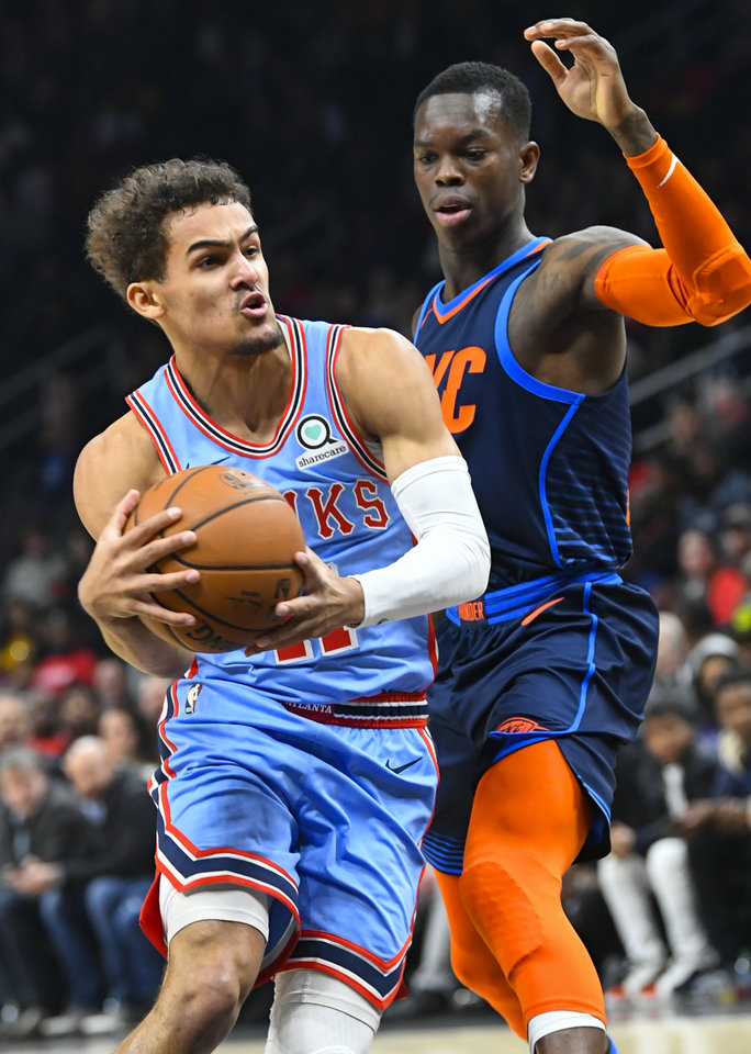 Photo - Atlanta Hawks guard Trae Young gets past the defense of Oklahoma City Thunder guard Dennis Schroder, right, during the second half of an NBA basketball game, Tuesday, Jan. 15, 2019, in Atlanta. The Hawks won 142-126. (AP Photo/John Amis)