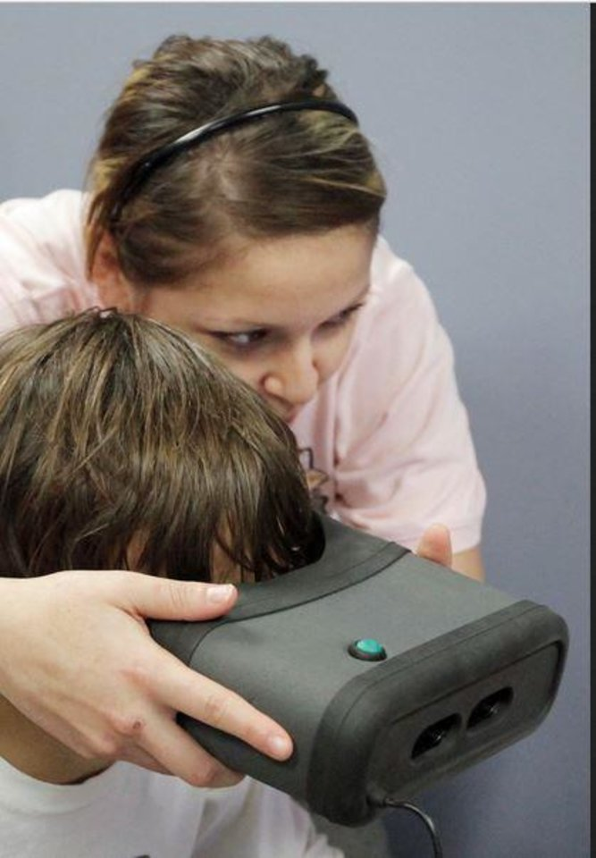 Photo -  Gloria Gomez gives an iris scan in 2009 to a boy at the Oklahoma County Sheriff substation at the Oklahoma City Zoo. [Photo by Nate Billings, The Oklahoman Archives]