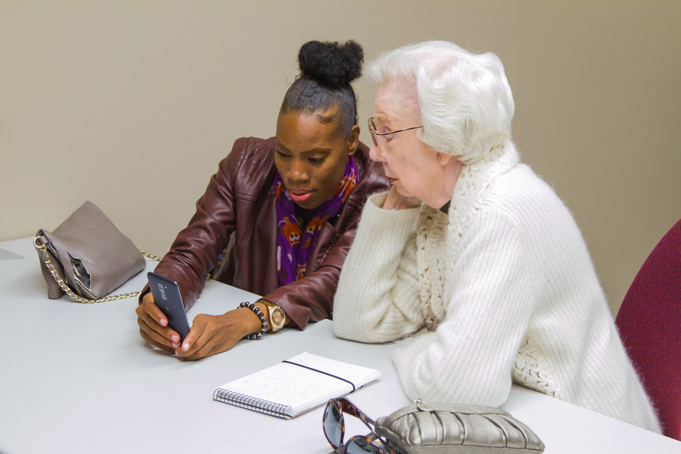 Photo -  Francis Tuttle IT student Tonyetta Hooks works on a smartphone with Concordia resident Virginia Olds. [PHOTO PROVIDED]