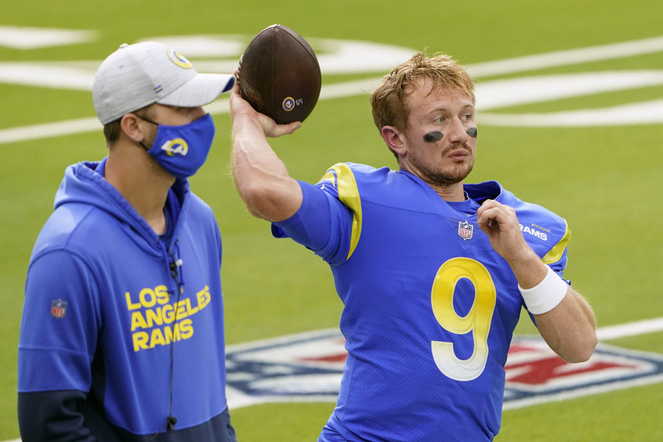 Photo -  Injured Los Angeles Rams quarterback Jared Goff, left, stands next to quarterback John Wolford (9) before an NFL football game against the Arizona Cardinals in Inglewood, Calif., Sunday, Jan. 3, 2021. Jared Goff is trying to return for the Los Angeles Rams' playoff game at Seattle just 13 days after thumb surgery. If he can't go, backup John Wolford will make his second NFL start. The Rams (10-6) are confident they can win with either man behind center. (AP Photo/Jae C. Hong)
