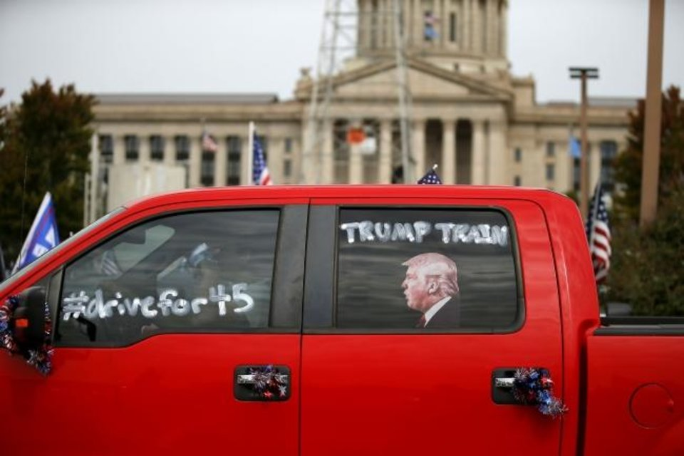 Photo -  A truck decorated to show support for President Donald Trump drives in a parking lot at the state Capitol during a MAGA DRAG the Interstate event Saturday.  [Bryan Terry/The Oklahoman]
