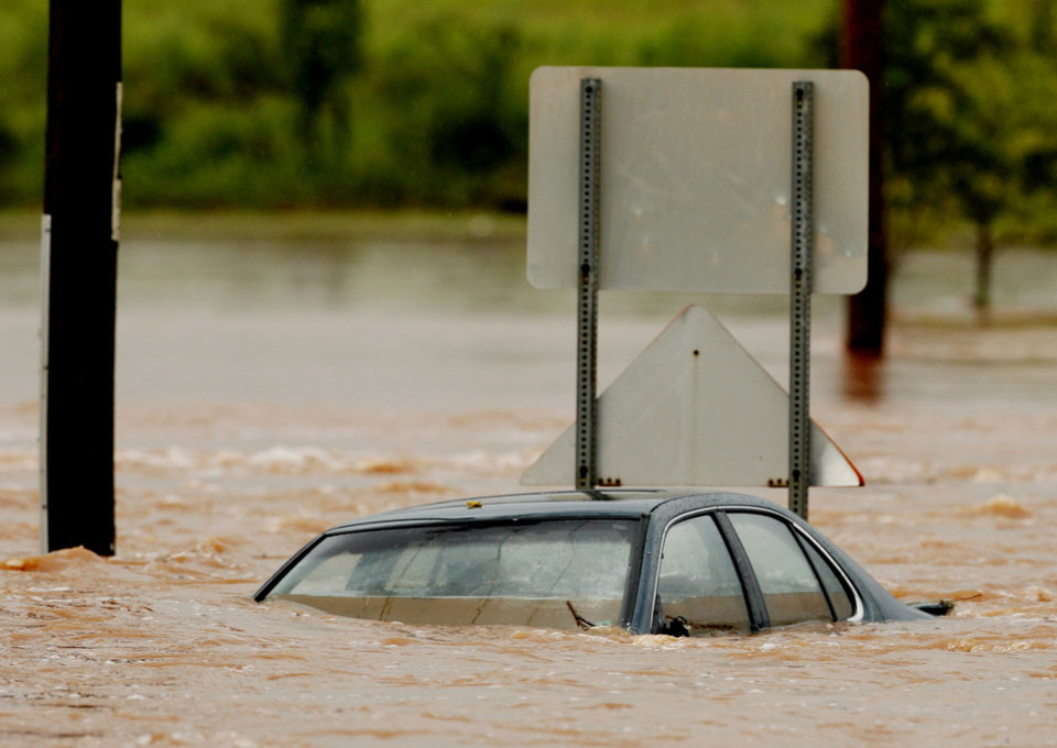 Photo - A car is full of water at Franklin Road and N.E. 24th after flooding in Norman, Oklahoma on Sunday, August 19, 2007.  A policeman on the scene was unaware of the condition or location of the driver.   BY STEVE SISNEY, THE OKLAHOMAN