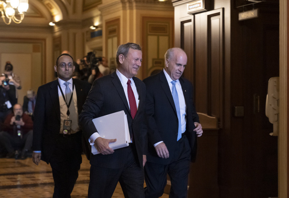Photo -  Chief Justice of the United States John Roberts arrives at the Senate to preside at the impeachment trial of President Donald Trump on charges of abuse of power and obstruction of Congress, at the Capitol in Washington, Thursday, Jan. 16, 2020. He is escorted by Senate Sergeant at Arms Michael Stenger, right. (AP Photo/J. Scott Applewhite)