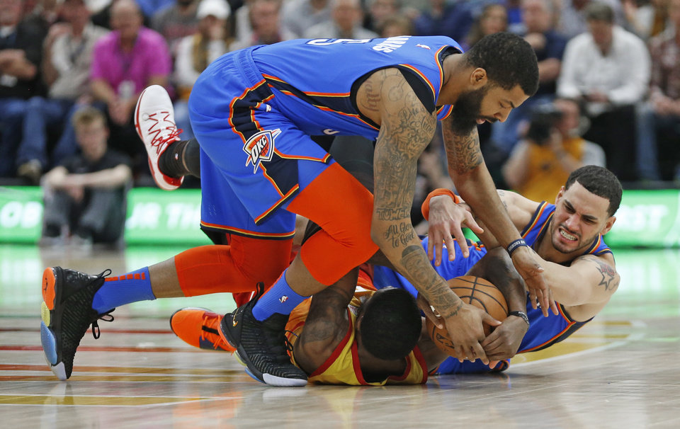 Photo - Utah Jazz forward Royce O'Neale, bottom, battles for the ball against Oklahoma City Thunder's Abdel Nader, right, and Markieff Morris, top, in the first half during an NBA basketball game Monday, March 11, 2019, in Kearns, Utah. (AP Photo/Rick Bowmer)