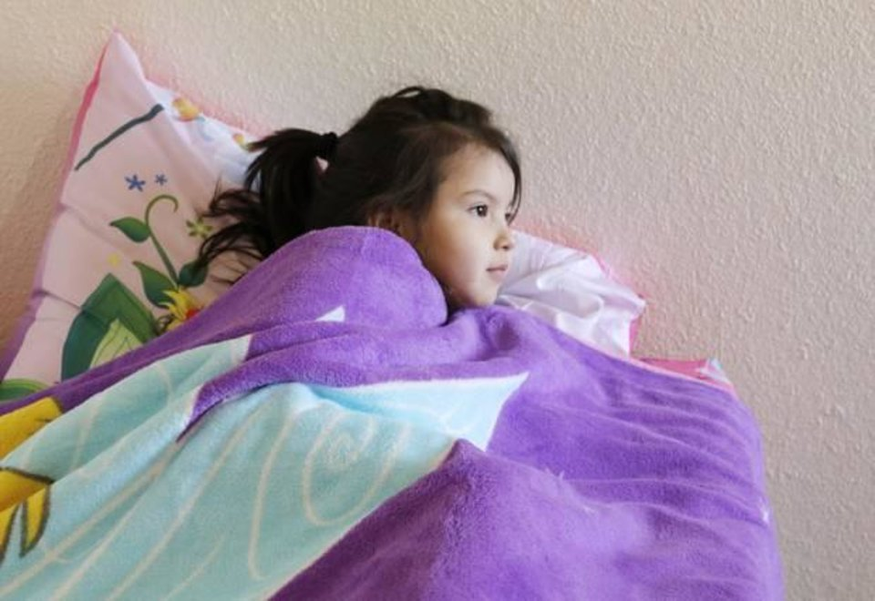 Fabulous Ryleigh Genn curls up under the blanket of her new bed during a delivery for Hope Chest Ministries in Oklahoma City Saturday February
