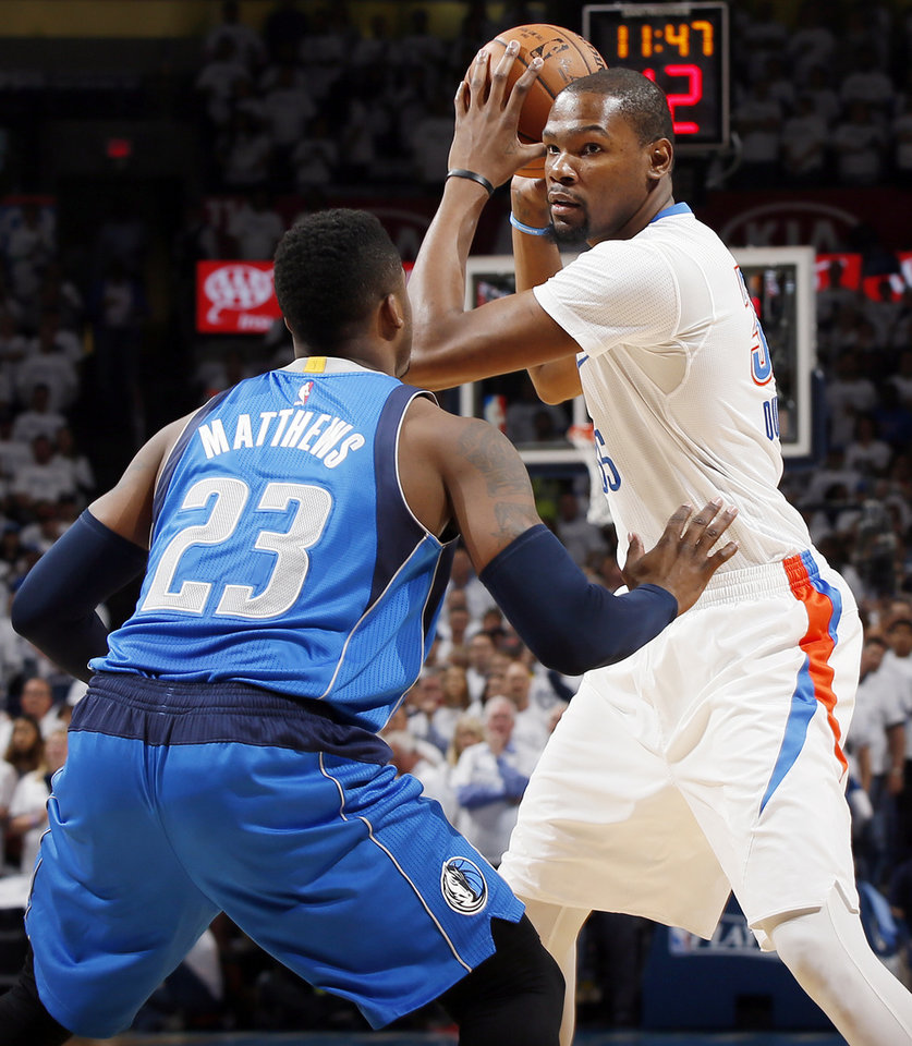 Photo - Oklahoma City's Kevin Durant (35) holds the ball as Dallas' Wesley Matthews (23) defends during Game 2 of the first round series between the Oklahoma City Thunder and the Dallas Mavericks in the NBA playoffs at Chesapeake Energy Arena in Oklahoma City, Monday, April 18, 2016. Photo by Nate Billings, The Oklahoman