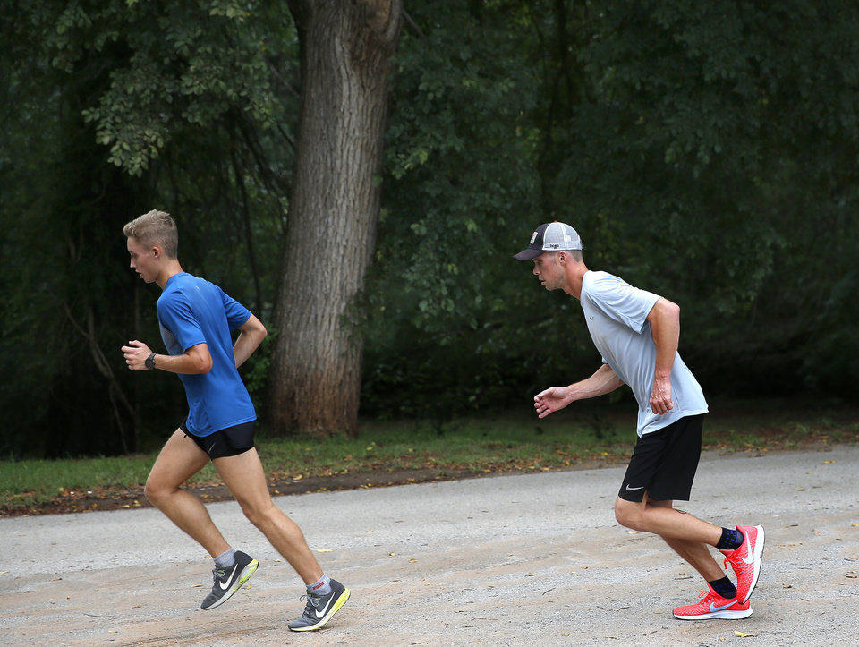 Photo - Guthrie's Trevor Sallee, left, runs with his coach, James Strahorn, on Sept. 4, 2018. Sallee finished in second place at the Choctaw Jacket Run on Friday. [Sarah Phipps/The Oklahoman]