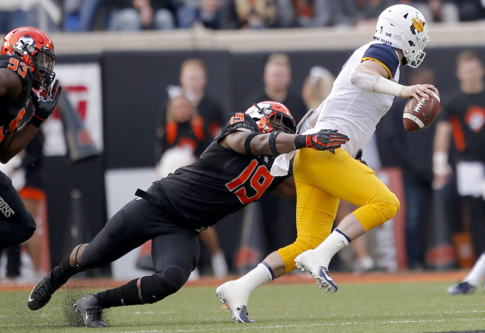 Photo - Oklahoma State's Justin Phillips (19) sacks West Virginia's Will Grier (7) in the first quarter during a college football game between the Oklahoma State Cowboys (OSU) and the West Virginia at Boone Pickens Stadium in Stillwater, Okla., Saturday, Nov. 17, 2018. OSU won 45-41.Photo by Sarah Phipps, The Oklahoman