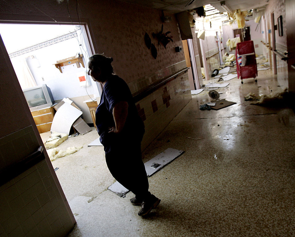 Photo - Natta Wood, an employee at the nursing home, looks at storm damage at the nursing home in Geary on Sunday, August 19, 2007 following a storm that hit the area early Wednesday morning. By John Clanton, The Oklahoman