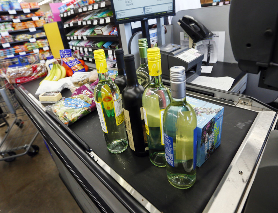 Photo -  Wine and beer sits on the conveyor belt at a checkout lane next to groceries inside the Homeland grocery store at Classen and NW 18 on the first day of wine and strong beer sales in grocery stores, in Oklahoma City, Monday, Oct. 1, 2018. [Nate Billings/The Oklahoman]