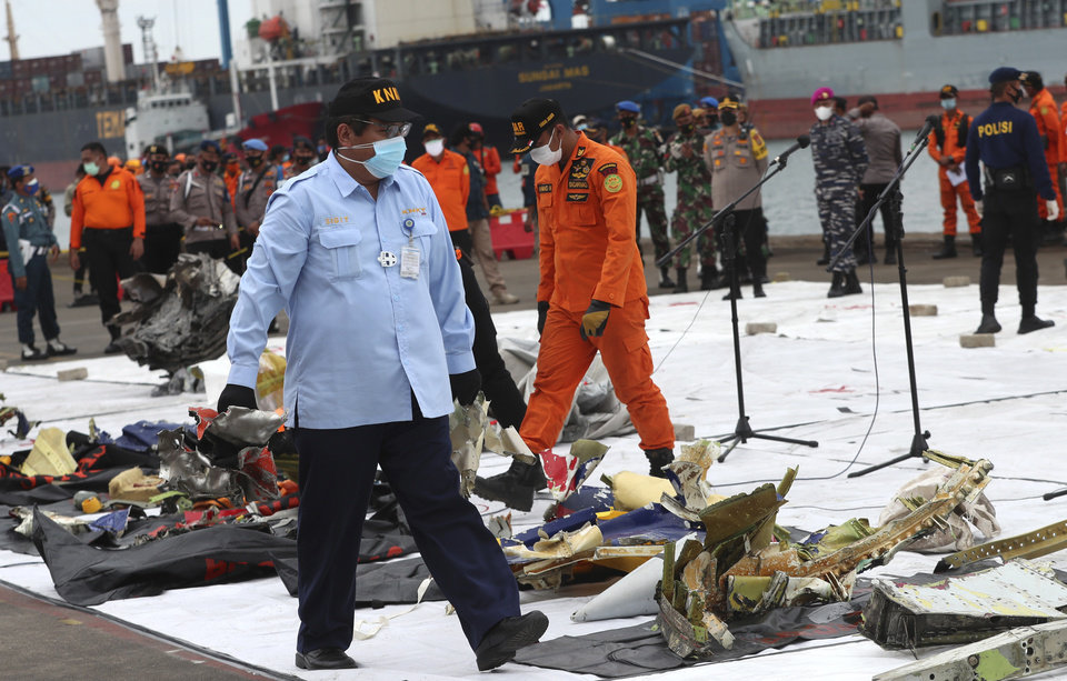 Photo -  An Indonesian National Transportation Safety Committee (KNKT) investigator inspects the debris found in the waters around the location where Sriwijaya Air passenger jet crashed, at Tanjung Priok Port in Jakarta, Indonesia, Monday, Jan. 11, 2021. The search for the black boxes of a crashed Sriwijaya Air jet has intensified to boost the investigation into what caused the plane carrying dozens of people to nosedive into Indonesia seas. The Boeing 737-500 jet disappeared during heavy rain on Saturday. (AP Photo/Achmad Ibrahim)