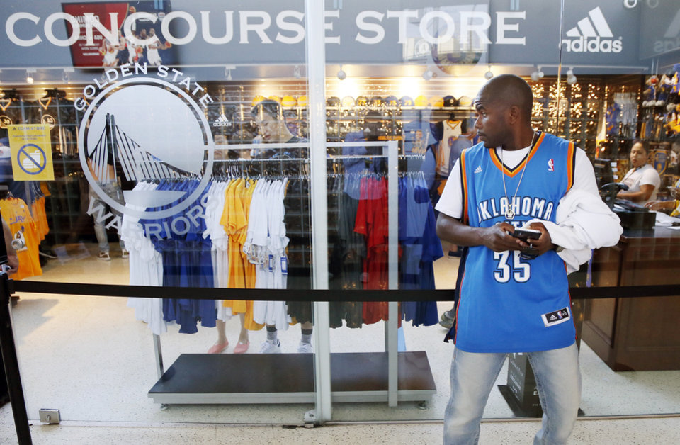 Photo - Thunder fan Henry Crockett, of Las Vegas, uses his phone in front of a Warriors team store before Game 2 of the Western Conference finals in the NBA playoffs between the Oklahoma City Thunder and the Golden State Warriors at Oracle Arena in Oakland, Calif., Wednesday, May 18, 2016. Crockett became a fan of Kevin Durant because he also grew up in the Washington D.C. area. Photo by Nate Billings, The Oklahoman