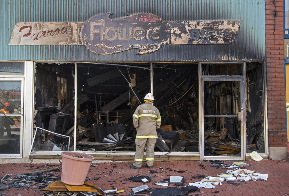 Photo - A Guthrie firefighter looks over the damage of a fire that destroyed two businesses Guthrie, Okla. on Monday, Feb. 25, 2019.    Photo by Chris Landsberger, The Oklahoman