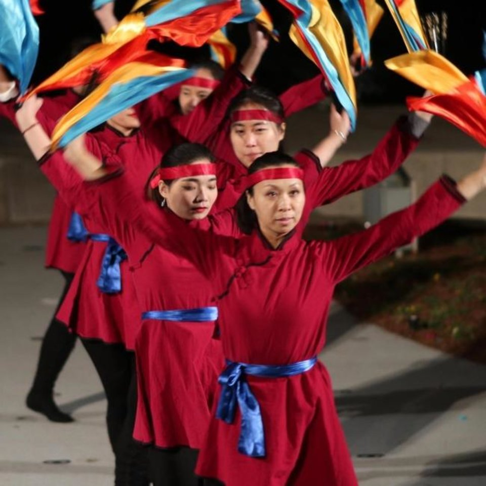 Photo -  Members of the Confucius Institute at the University of Oklahoma perform a folk dance Feb. 16, 2018, on the Water Stage during the Lunar New Year celebration at the Myriad Botanical Gardens. [Doug Hoke/The Oklahoman Archives]