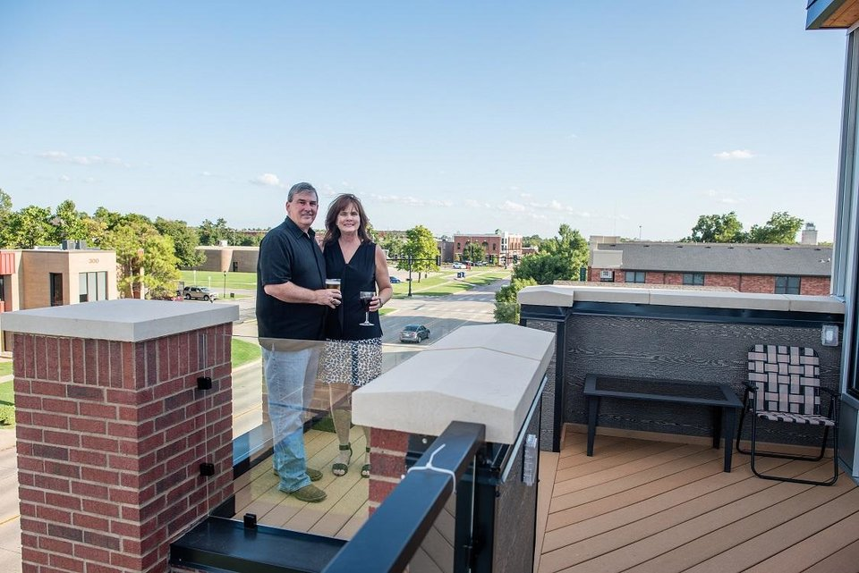 Photo -  David and Julie Chapman enjoy a view of downtown Edmond from the rooftop patio of their home along Broadway. [Photo by Eriech Tapia for The Oklahoman]