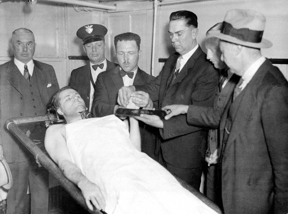 "Photo - **ADVANCE FOR MONDAY FEB 2** The body of Charles ""Pretty Boy"" Floyd is propped on a slab in the county morgue in East Liverpool, Ohio, after he was shot and killed in a gun battle with federal agents on a nearby farm, Oct. 22, 1934.  The officers in the background from left  are, Chief Hugh J. McDermott, G.G. Montgomary, Chester Smith, Herman Roth and E.G. Sturgis. On the centennial of  Floyd's birth, the notorious bank robber and mass murderer is still remembered asa Robin Hood in his home states of Oklahoma and Arkansas, celebrated in pop culture and credited with bringing the FBI to prominence. (AP Photo)"