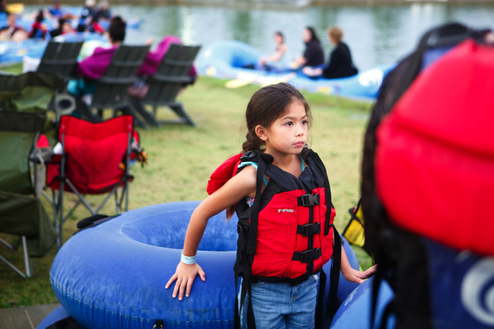 Photo -  Emmie Jones, 8, waits for her mother to return so the family can get into their tubes for Riversport OKC's Floating Films on Saturday night in Oklahoma City. [Photo by Anya Magnuson, The Oklahoman]