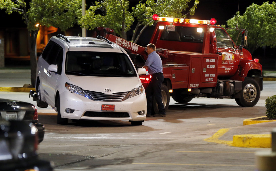 Photo - A white van is towed from a Braum's restaurant on May and NW 112th St. in Oklahoma City where Labor Commissioner Mark Costello was fatally stabbed, Sunday, Aug. 23, 2015.  Photo by Nate Billings, The Oklahoman