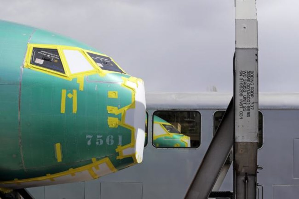 Photo -  The front of a Boeing 737 fuselage, eventually bound for Boeing's production facility in nearby Renton, Wash., sits on a flatcar rail car and is reflected in a nearby passenger train car at a rail yard in Seattle. [AP PHOTO]