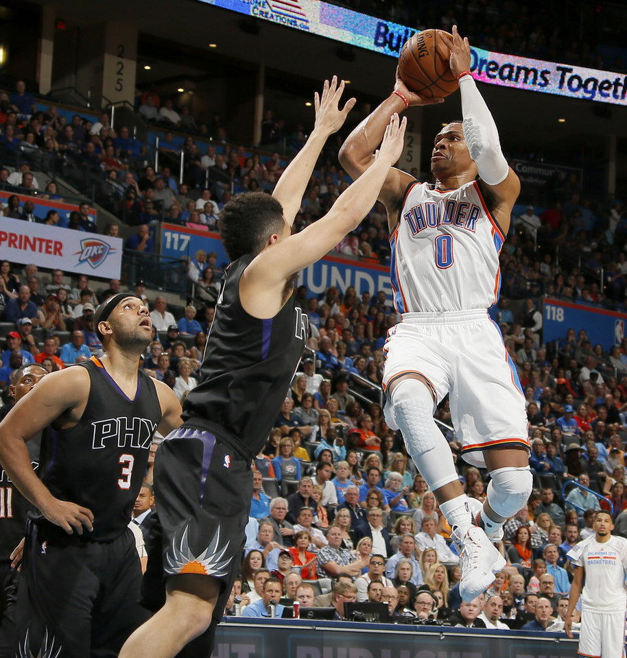 Photo - Oklahoma City's Russell Westbrook (0) goes to the basket in front of Phoenix's Jared Dudley (3) and Devin Booker (1) during an NBA basketball game between the Oklahoma City Thunder and the Phoenix Suns at Chesapeake Energy Arena in Oklahoma City, Friday, Oct. 28, 2016. Photo by Bryan Terry, The Oklahoman