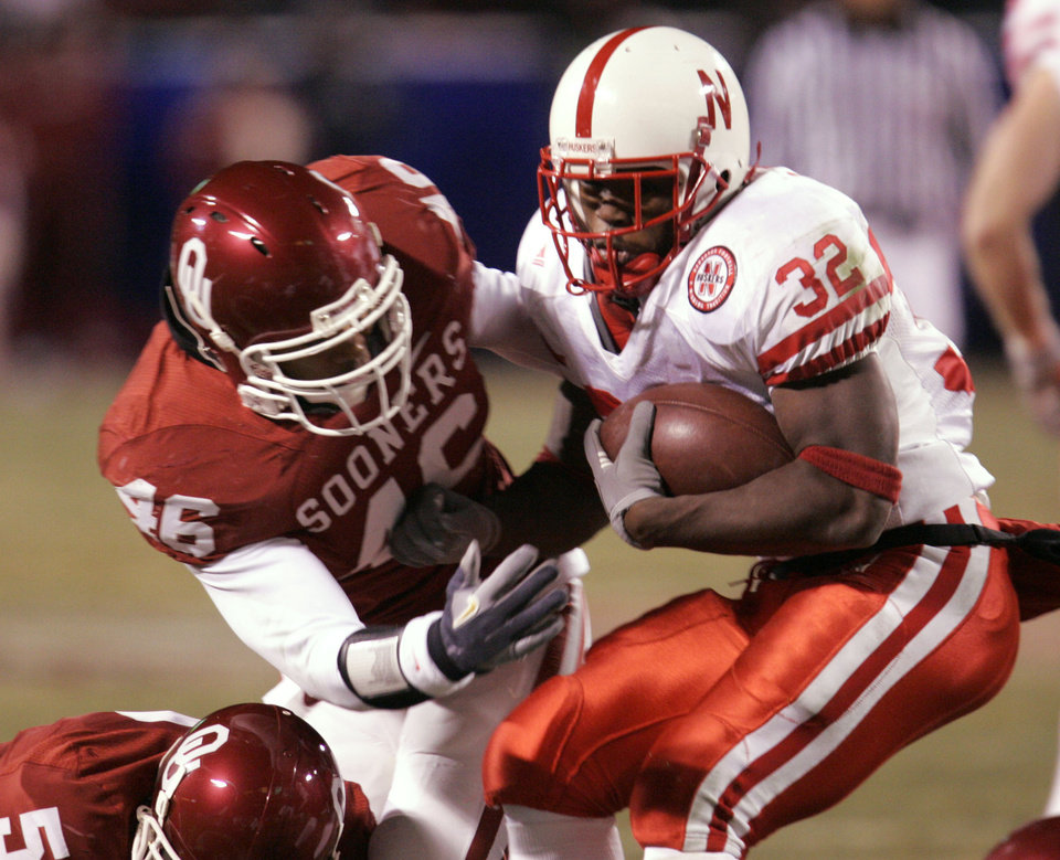 Photo - Nebraska's Brandon Jackson (32) is stopped by Oklahoma's Zach Latimer (46) in the first half of the Big 12 Championship game during the University of Oklahoma Sooners (OU) college football game against the University of Nebraska Cornhuskers (NU) at Arrowhead Stadium, on Saturday, Dec. 2, 2006, in Kansas City, Mo.   by Chris Landsberger, The Oklahoman  ORG XMIT: KOD