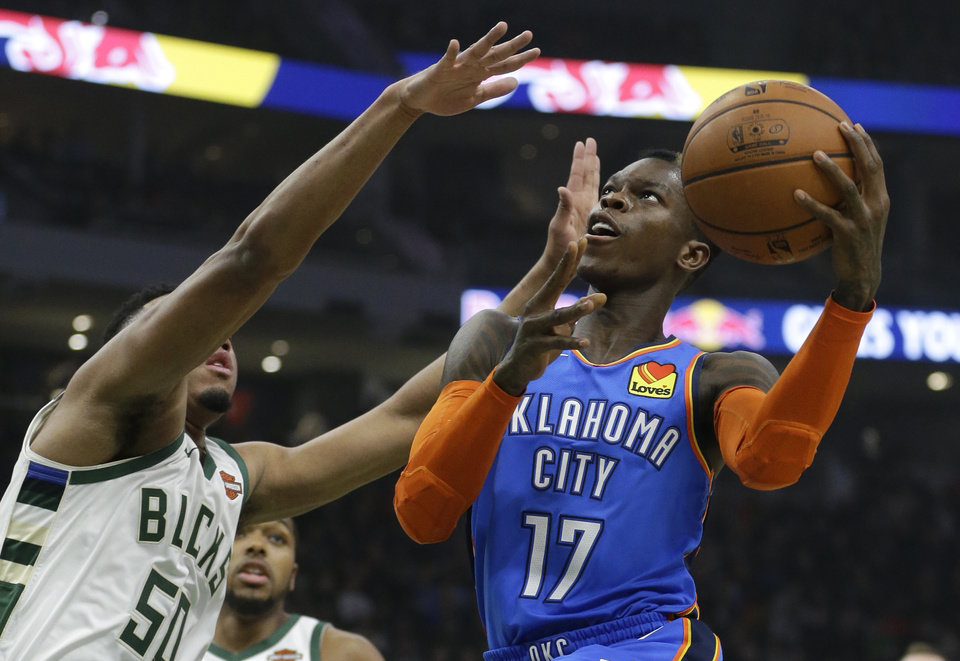 Photo - Oklahoma City Thunder's Dennis Schroder shoots against Milwaukee Bucks' Bonzie Colson during the first half of an NBA basketball game Wednesday, April 10, 2019, in Milwaukee. (AP Photo/Aaron Gash)