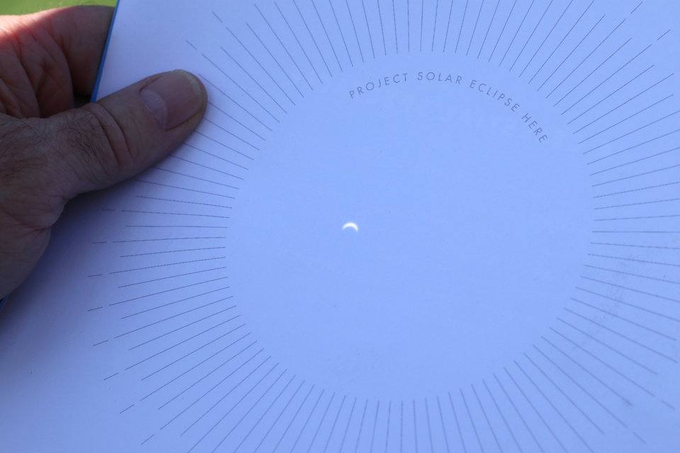 Photo - Image of the eclipse projected on a card through a paper plate with a pinhole in it during the great American solar eclipse party on the Great Lawn of the Myriad Botanical Gardens Monday, August 21, 2017. Photo by Doug Hoke, The Oklahoman
