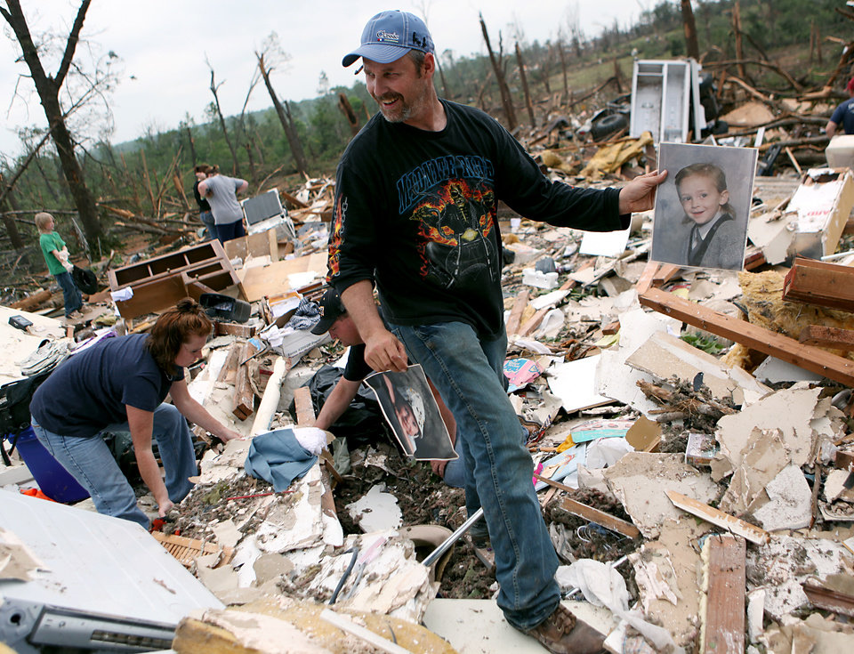 Photo - Keith Bolles talks with family members and friends as he celebrates finding pictures of his son at his destroyed home in Little Axe, Oklahoma on Tuesday, May 11, 2010. By John Clanton, The Oklahoman