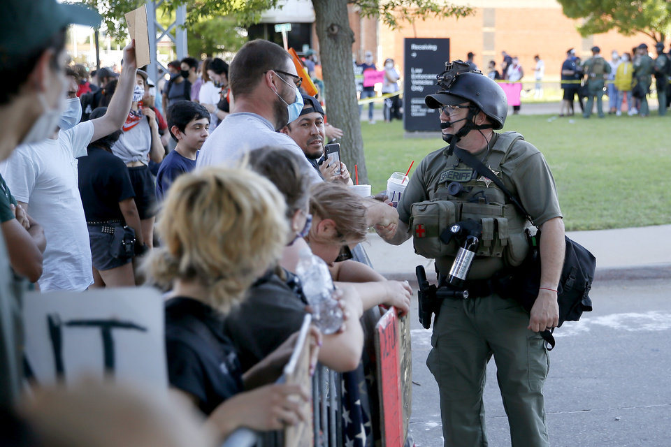 Photo - A member of the Oklahoma County Sherriff's Office shakes hands with protesters outside the Oklahoma County jail in Oklahoma City on Sunday, May 31, 2020. The Black Lives Matter protest was in response to the death of George Floyd. [Bryan Terry/The Oklahoman]