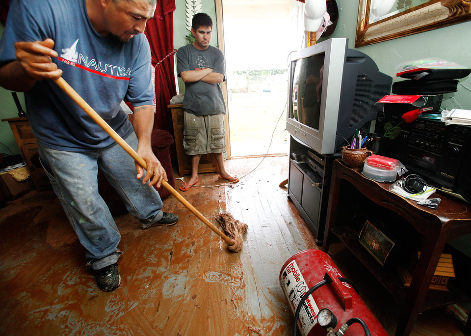 Photo - FLOOD / CLEANUP / CLEAN UP: Abel Borrego mops muddy water from the floor of the living room in his house on the east bank of Lightning Creek near SW 28 and S Santa Fe. Residents cleaned homes and yards in the area near Lightning Creek in south Oklahoma City, Friday, July 9, 2010. Heavy rains last night caused the  creek to overflow its banks, flooding the areas on both sides of the creek.  Staff Photo by Jim Beckel , The Oklahoman ORG XMIT: KOD