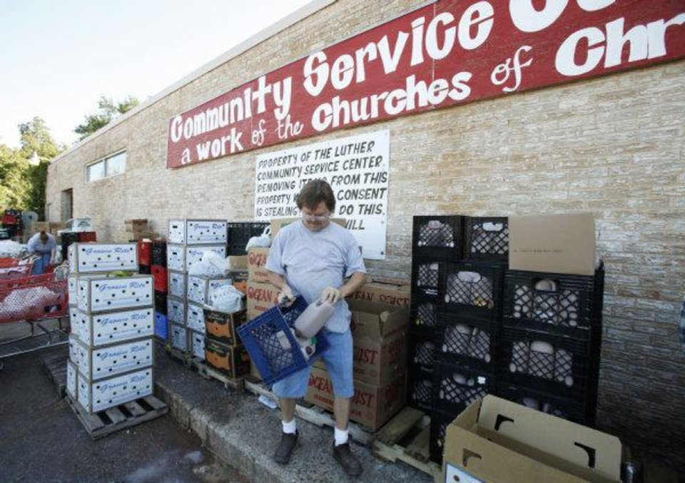 Photo - Volunteer Robert Stone loads groceries at the Luther Community Service Center.  PHOTO BY STEVE GOOCH, THE OKLAHOMAN  Steve Gooch - The Oklahoman