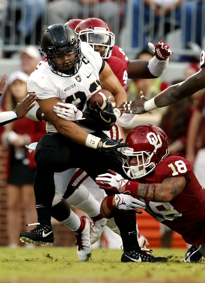 Photo - Oklahoma's Curtis Bolton (18) tries to tackle Army's Darnell Woolfolk (33) during a college football game between the University of Oklahoma Sooners (OU) and the Army Black Knights at Gaylord Family-Oklahoma Memorial Stadium in Norman, Okla., on Saturday, Sept. 22, 2018. Photo by Steve Sisney, The Oklahoman