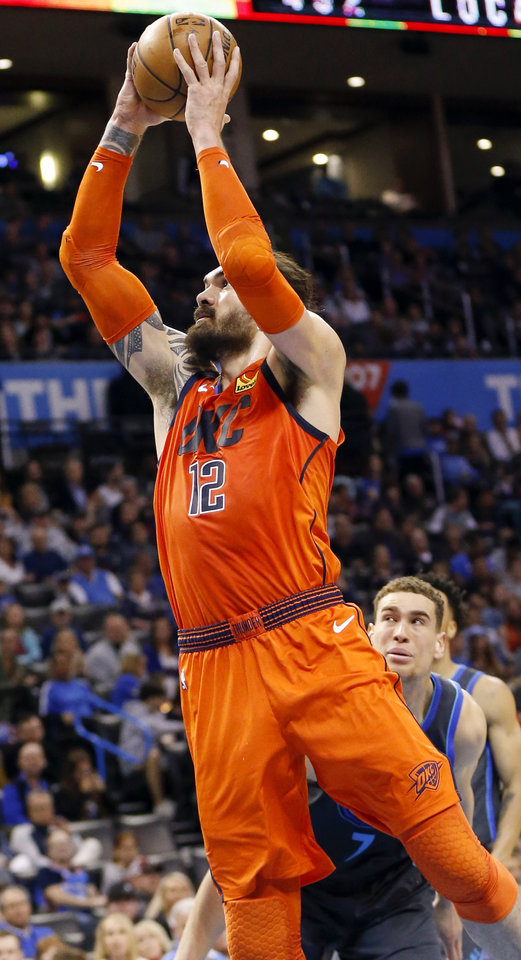 Photo - Oklahoma City's Steven Adams (12) goes to the basket past Dallas' Dwight Powell (7) in the second quarter during an NBA basketball game between the Dallas Mavericks and the Oklahoma City Thunder at Chesapeake Energy Arena in Oklahoma City, Sunday, March 31, 2019. Photo by Nate Billings, The Oklahoman
