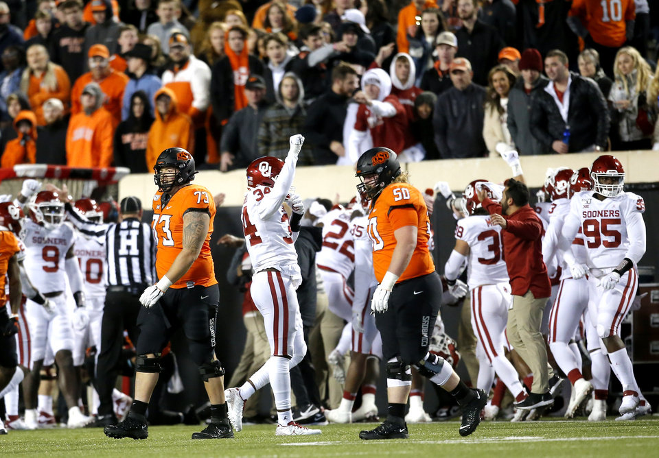 Photo - Oklahoma's David Ugwoegbu (34) celebrates an Oklahoma interception in the fourth as Oklahoma State's Teven Jenkins (73) and Relijah Sherman (50) walk off the field  during the Bedlam college football game between the Oklahoma State Cowboys (OSU) and Oklahoma Sooners (OU) at Boone Pickens Stadium in Stillwater, Okla., Saturday, Nov. 30, 2019. OU won  34-16. [Sarah Phipps/The Oklahoman]