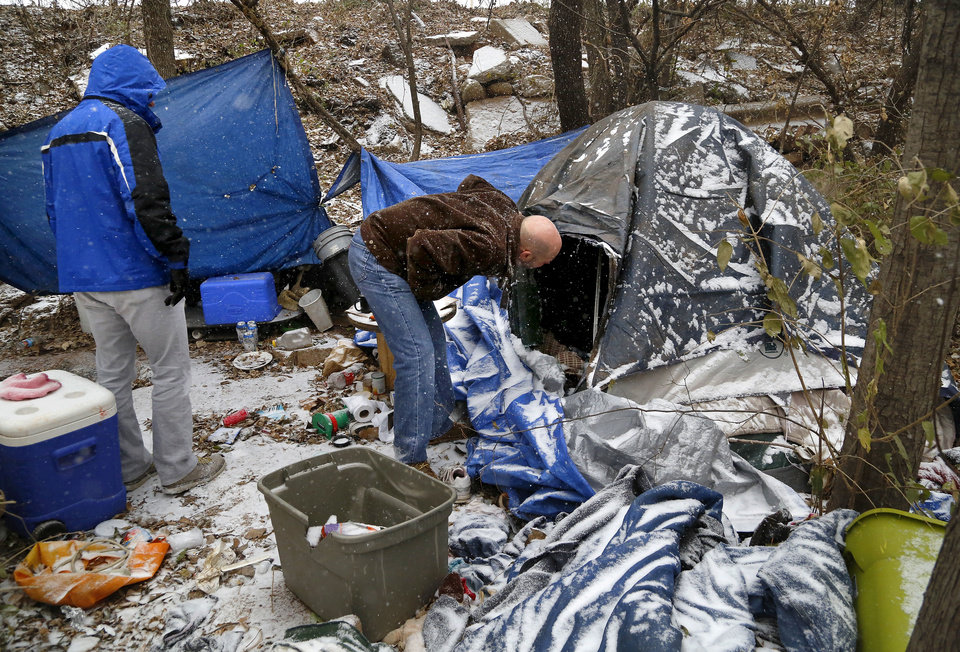 Photo - Jonathon Roberts checks to see if anyone is inside this tent as he and another volunteer with Be the Change, an Oklahoma City based non-profit that provides assistance to the homeless,  walk through a homeless encampment near NW 10 and Villa, as they visited several locations known to be frequented by the homeless west of the downtown area Thursday afternoon, Dec. 5, 2013. No one was inside the tents at this location when Roberts stopped by this afternoon. In preparation for this week's winter storms,  homeless shelters and organizations are ramping up efforts to house people during the coldest days the state has seen in several years. This includes actively going out to documented homeless camps and trying to convince people to accept a ride to an indoor shelter in Oklahoma City, but not everyone agrees to abandon their camps, some out of a fear that their material possessions will be stolen while they're gone.  Photo by Jim Beckel, The Oklahoman  Jim Beckel - THE OKLAHOMAN