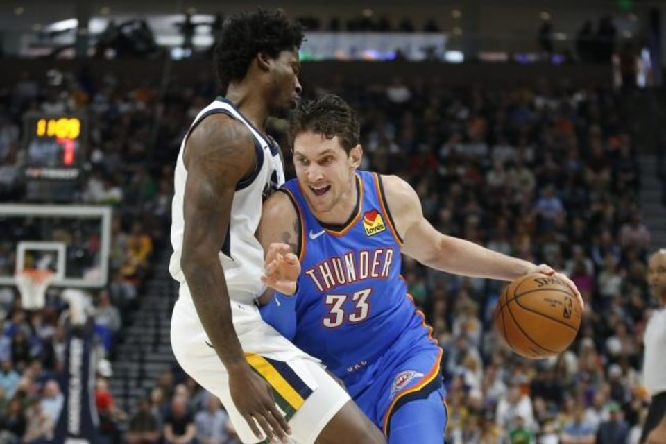 Photo -  Oklahoma City Thunder forward Mike Muscala, right, drives in to Utah Jazz center Ed Davis during Wednesday night's game in Salt Lake City. Utah won the game 100-95. [AP Photo/Rick Bowmer]